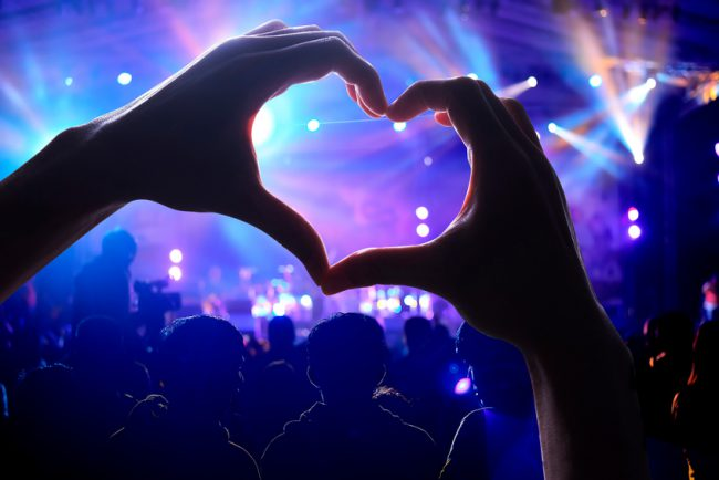 Crowd of Audience at during a concert with a heart shaped hands shadow